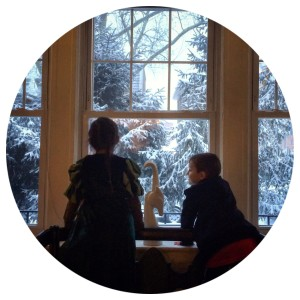 kids looking out a snowy window